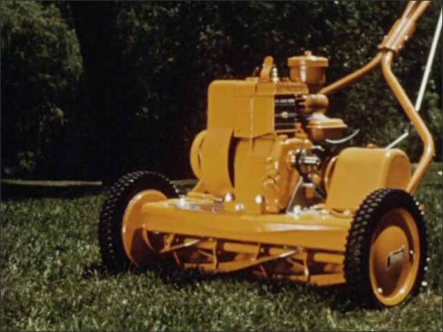 1960s: A shiny yellow lawnmower on a grass lawn in front of classic green station wagon. Mower on grass. Man grabs mower handles and mows his lawn.
