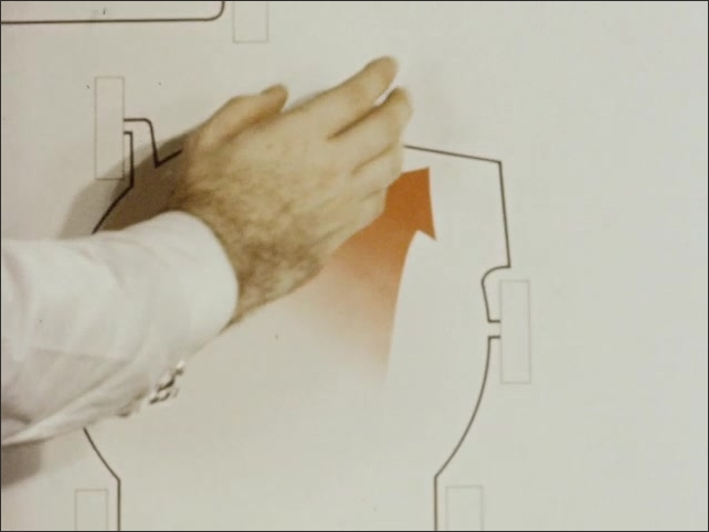 1960s: A man's hands point to various illustrated diagrams of rotary lawnmowers on a white board. One has an orange arrow that he mimics with his hand.
