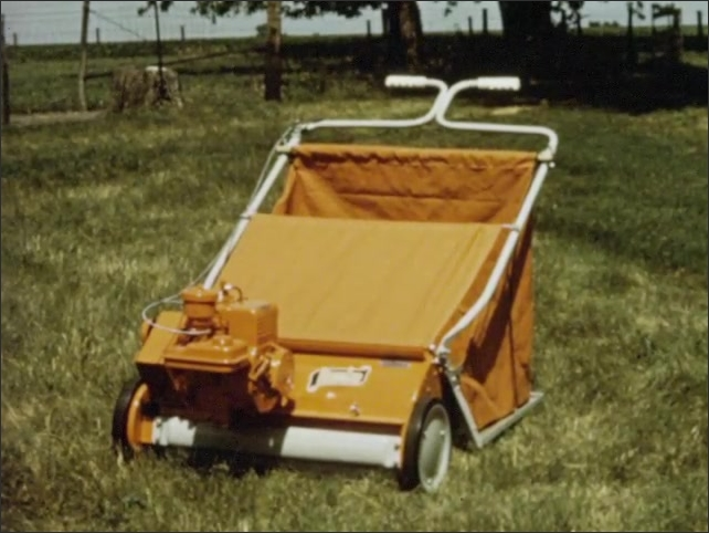 1960s: Two lawn-sweepers, one model is self-propelled. Man pushes lawn-sweeper across yard. Woman walks dog behind yellow lawnmower.