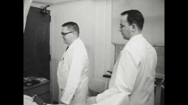 1960s Baltimore: Group of young male doctors gathers around a hospital bed doing rounds. Doctor examines the eyes of Black female lying in hospital bed. Exterior domed building.