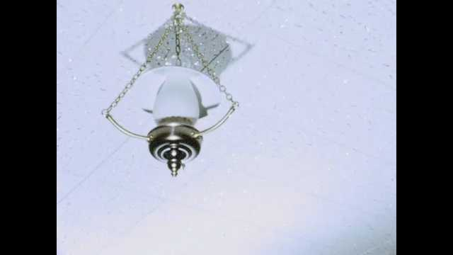 1960s: Light fixture on ceiling. Light on ceiling. Lamp next to curtains. Pot hangs on wall. Wall. Unfinished walls. Unfurnished room. Furnished room. Sign. People in furnishing store.
