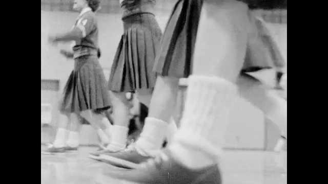 1960s: Cheerleaders at basketball game. Basketball players on bench. Cheerleaders perform for whole gymnasium.