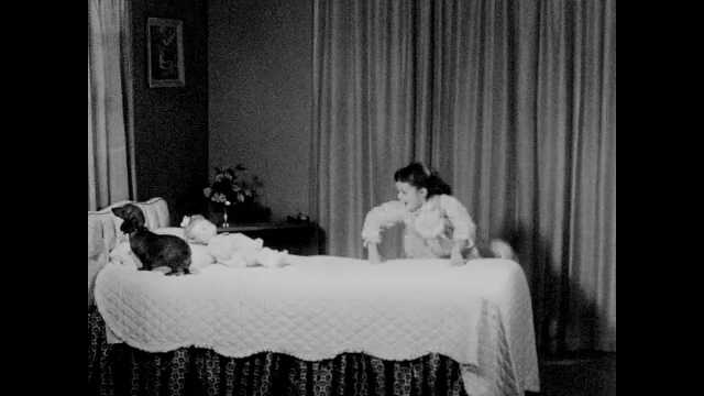 1960s: Girl climbs onto bed with dachshund and doll. Girl in bed and plays with and embraces doll. Dog tilts its head. Girl listens to doll's heart with stethoscope.