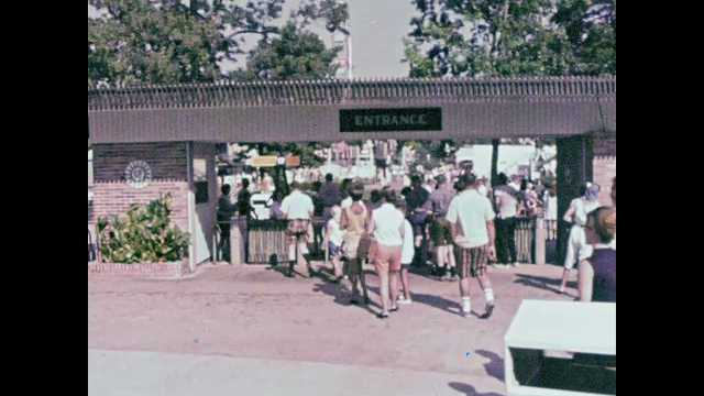 1960s: People enter amusement park and receive bracelets. People walk through amusement park. People ride roller coasters and rides. People ride carousel. People walk through old West town.