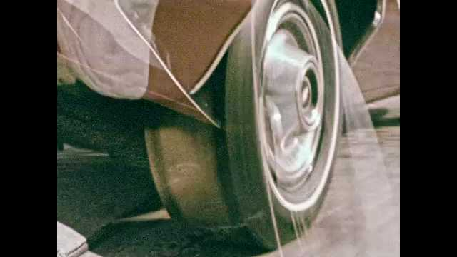 1960s: Car tires spin on paved roads. Car drives over railroad tracks. Cars drive past pedestrians in city. Car drives on curvy wooded road. Car drives over rocks. Car tire sits on pavement.