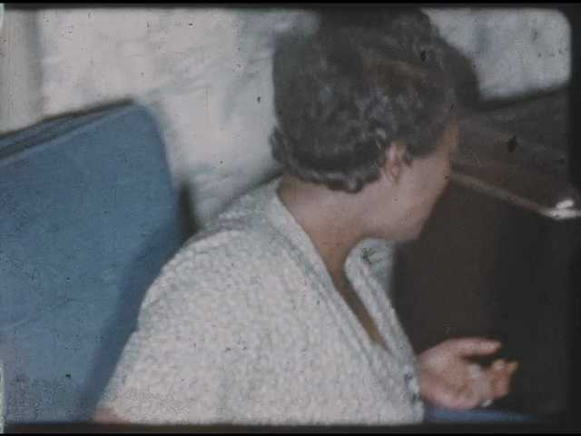 1960s: Woman sitting, pan to man on couch, man talking.