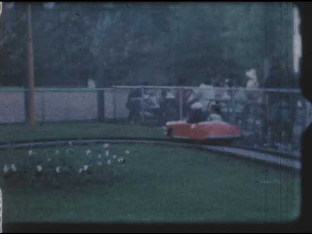 1960s: Kids driving toy car on track. Boy driving toy tractor on track.