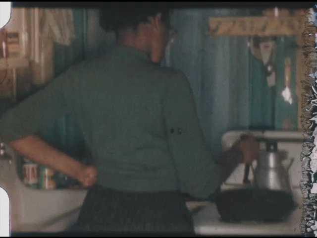 1960s: Woman stands at stove and stirs pot. Woman sits at table and eats. Woman wearing apron.