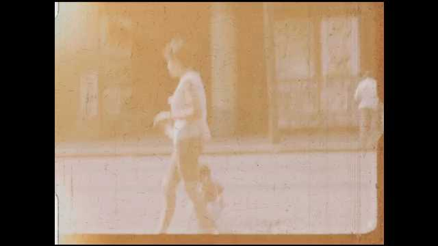 1960s: City street.  Woman walks along with baby and dog.