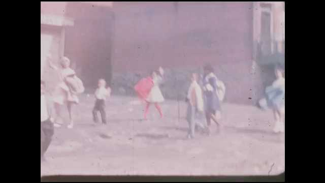 1960s: Group of kids walk across empty lot, wave. Woman stands on corner. Man and child run across street. Men and women in convertible. Man and woman walk across lot, woman hides behind man.