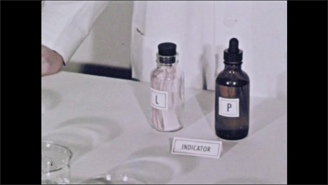 1950s: Five jars of liquid in row. Person sets down two dropper bottles and a label in front.