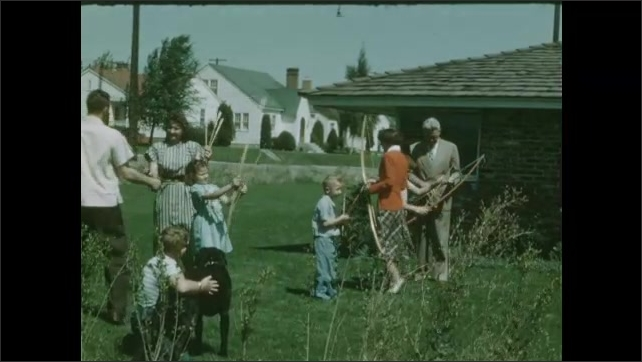 1950s: Line of five girls in blue shorts try archery. Group of men and women in casual clothes practice archery on field. Family practice archery on front lawn. Girl in white practices archery.