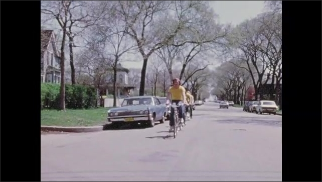 1970s: Close up of boy talking. Police officer talking. Officer gives pamphlet to boy, zoom in. Officer points. Boys riding bikes in line. High angle, boys riding bikes.