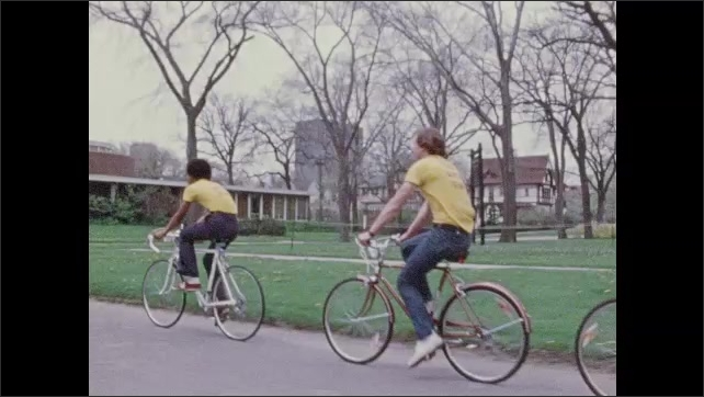 1970s: Tracking shot, boy riding bike, zoom out, teens riding bikes in line.
