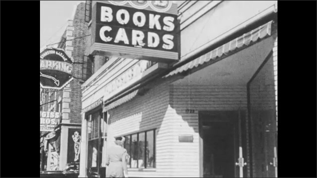 1950s: Woman and boy walk down street, look in store window, enter bookstore.