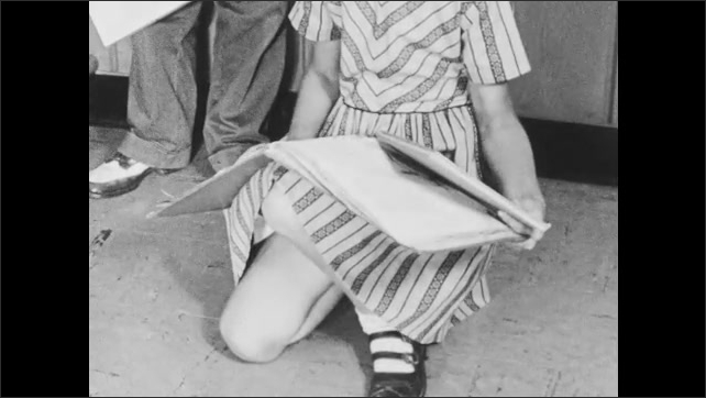 1950s: Girl takes book from shelf, knocks down another book. Girl picks up fallen book, brings it to the teacher.
