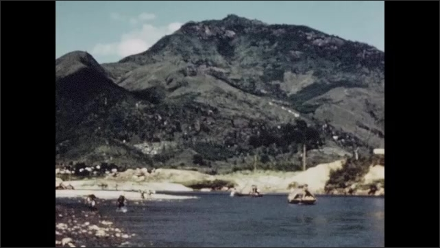 1950s: Water buffalo in river. People on shore of river, boats in water. Rafts on river. Man pushes reeds in water from shore.