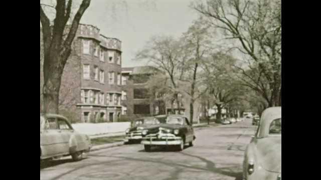 1950s: Cars drive past large apartment building.