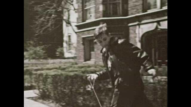 1950s: Boy walks dog down neighborhood street. Girl looks at parakeets in cage. Boy runs with dog on leash toward apartment building.