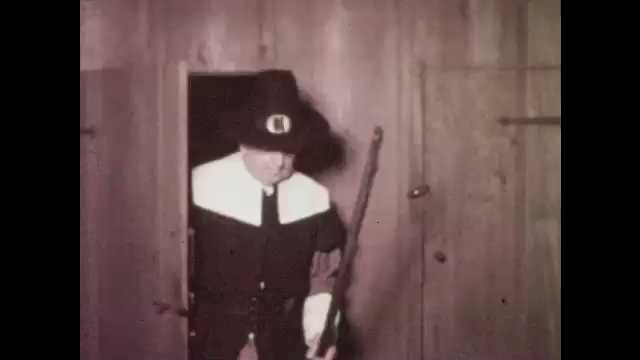1960s: Man walks into house, smiles, nods, hangs gun on rack. Woman hands man shirt.