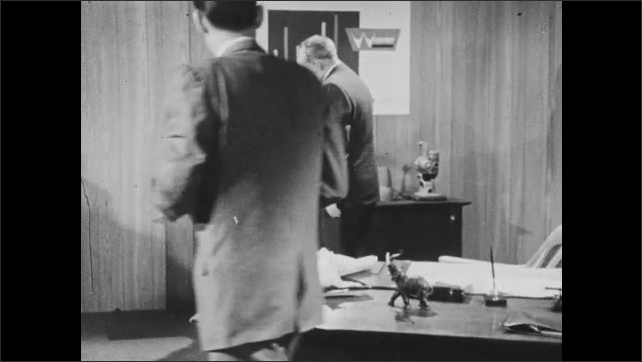 1960s: Man talking at desk. Man at desk, leans forward. Men stand from desk, walk to table. Close up of projector. Men talking by projectors. Hands assembling projector.
