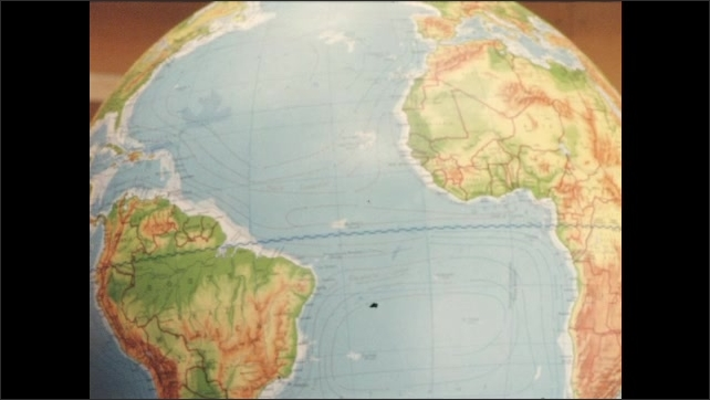 1960s: Boy walks up to desk and spins globe. Globe turns from Africa to Australia. Globe turns from Australia to South America.