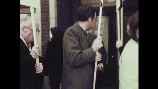 1970s: People walk, shout, carry signs in protest. Man from protest approaches man in doorway of building. Man talks. Two men argue.