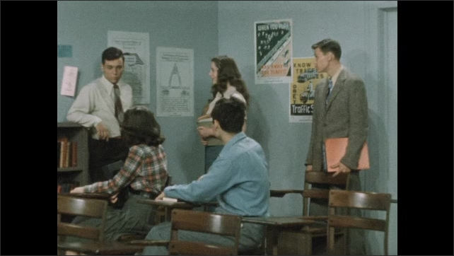 1950s: Three teen boys and two teen girls in a classroom. A girl and a boy sit in a desk and the others stand. All the teens talk animatedly and with concern, one boy agains the wall protesting.
