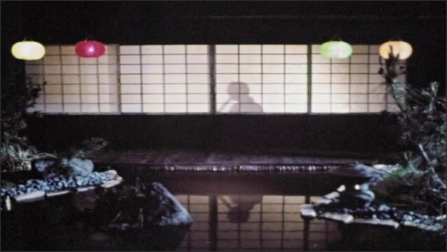 1960s: Reflection of man playing flute in pond. Shadow of man plays flute behind shoji doors. Woman in kimono opens shoji doors of house.