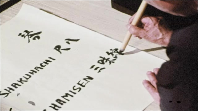 1960s: Man writes both English and kanji words on paper. Shamisen lies on floor. Man writes both English and kanji words on paper.  Woman hangs paper with words on display easel and speaks.
