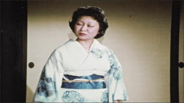1960s: Woman in kimono speaks and displays shakuhachi flute. Woman speaks and strikes her hand with shakuhachi flute.