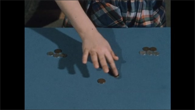 1950s: Girl counts change on table, sorts coins into piles, turns, talks, smiles.