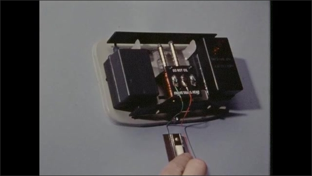 1970s: Cover of thermostat is removed. Coil and rods inside thermostat. Wires and rods. Interior bell with hammer and copper coils. Hand opens switch.