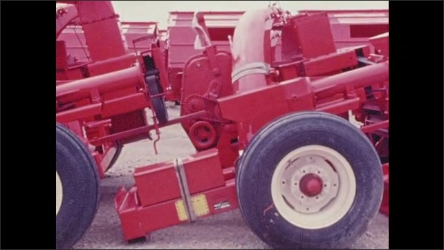 1970s: Farm equipment driving through field. Pan of farm equipment. Farm equipment in field. Cars on highway. Cars in parking lot, zoom out. Man puts gas pump in car.