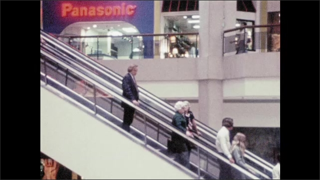 1970s: Hands assembling TV. Hand making circuit board. Man by loom. Shots of machine parts moving in factories. Man riding down escalator, zoom out. Man riding bike in parking lot, image freezes.
