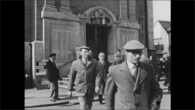1950s: People walk toward building. People walk out of polling station. Women walk down steps.