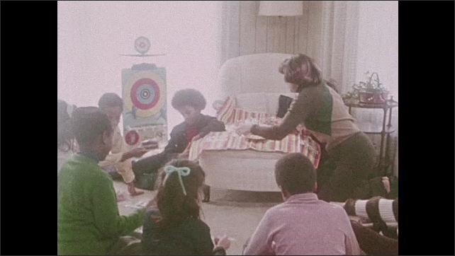 1970s: Close up of girl. Kids sitting on floor, woman hands out pieces of cake, zoom in on boy.