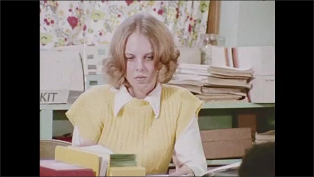 1970s: Woman at desk. Book on floor. Boy bends down to floor. Boy picks up book. High angle, boy standing. Woman at desk. Boy stands in foreground, walks to desk. Words on chalkboard.