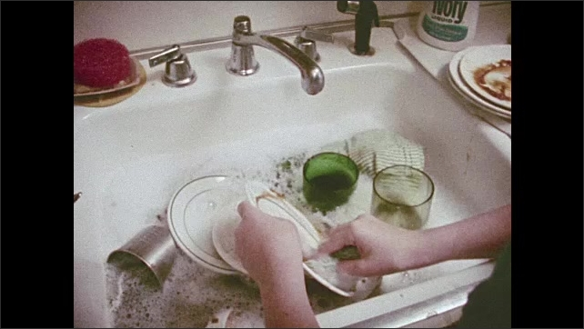 1970s: Girl picks up dishes, walks to sink. Girl watching TV in kitchen. Hands washing dishes. Girl washing dishes. Words spelled out on dishes. Girl watching TV.