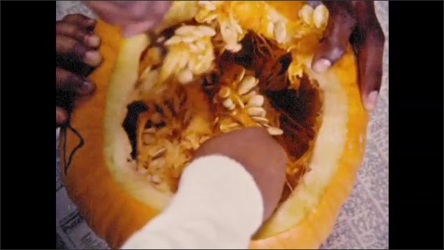 1970s: Man and girl in kitchen. Girl removes top of pumpkin. Man and girl scoop out pumpkin guts.