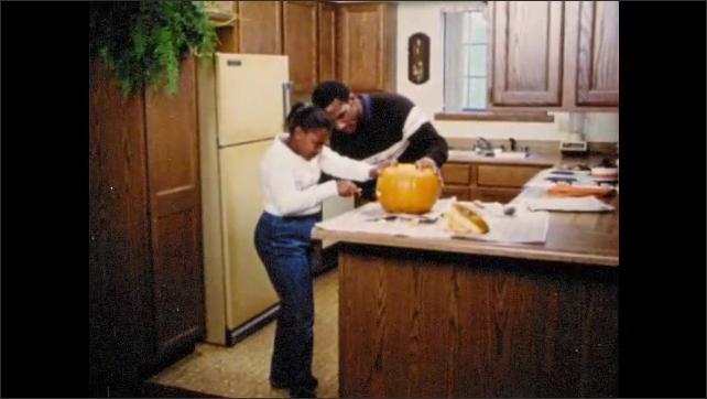 1970s: Man and girl carve pumpkin, girl pulls out piece of pumpkin. Cartoon Jack o Lantern talks.