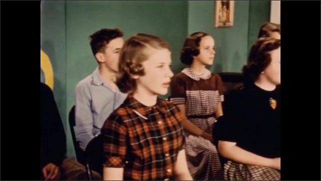 1950s: Classroom.  Music teacher conducts as students sing.  Woman points to diagram of music notes and speaks.