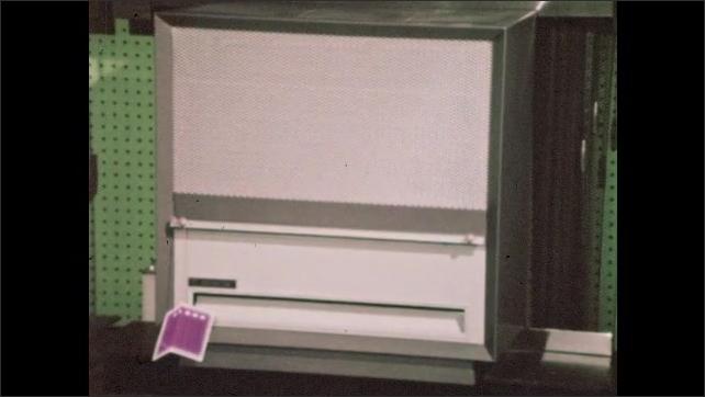 1960s: Store.  Man checks price tag on heater.  Man turns knob on air conditioner.