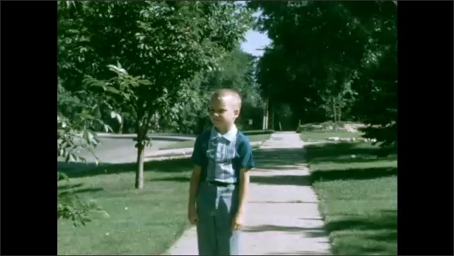 1950s: Cars driving down road pull over to side. Boy walking down sidewalk smiles.