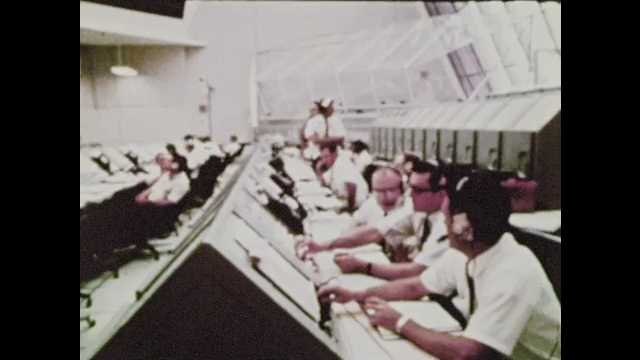 1970s: Men in NASA command center wear headphones, sit at monitors. Newspaper headline, astronauts come home. Office building, buses. Baseball game. Headline, Twins, Indians, Pirates, Braves.