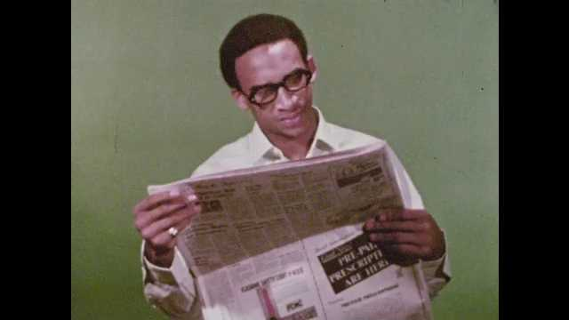 1970s: Man reads newspaper. Newsroom, people sit at desks, woman types, hands man paper. Municipal news, transportation, roads, sanitation, water. Men sit in office, woman walks in, gives paper.