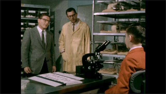 1950s: Man speaks to boy. Man nods. Men and boy leave room.