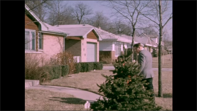 1950s: View of houses. Man and boy walk up sidewalk and enter home.