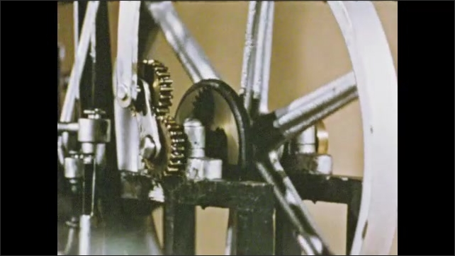 1950s: Close up of pistons moving. Model steam engine turning wheel. Gears moving. Cloud of steam. View of river. Ship model on fabric.