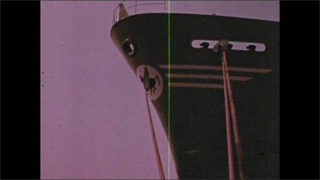 1970s: large ships moored in harbor with ropes in dim purplish light, ship's bow with thick ropes going down to dock, large industrial cranes and equipment in distance across water